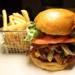 Mushroom burger with bacon on a brioche bun tomatoes lettuce and caramelized onions with basket of fries