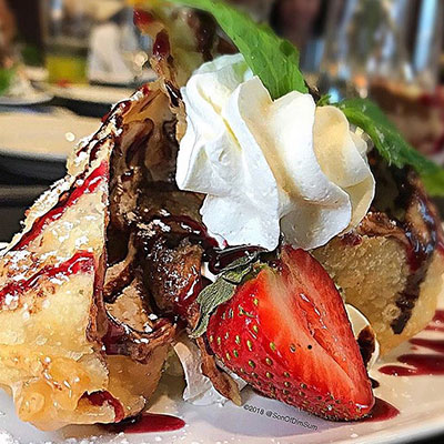 fried banana wonton with whipped cream and strawberries