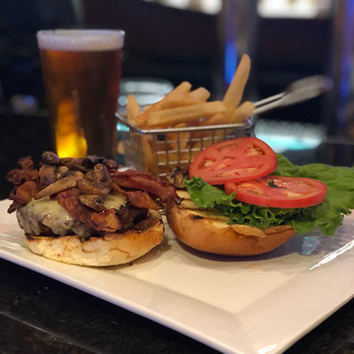 cheeseburger with mushrooms bacon lettuce and tomato accompanied by fries and beer